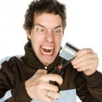 Young male about to cut a credit card on a white background